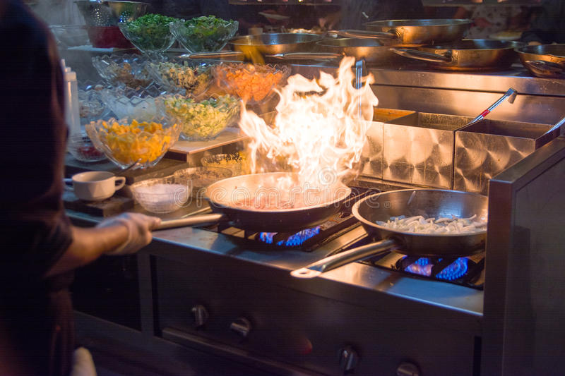 Chef in restaurant kitchen at stove with pan, doing flambe on food. low ligth selective focus. Chef in restaurant kitchen at stove with pan, flambe on food stock photo