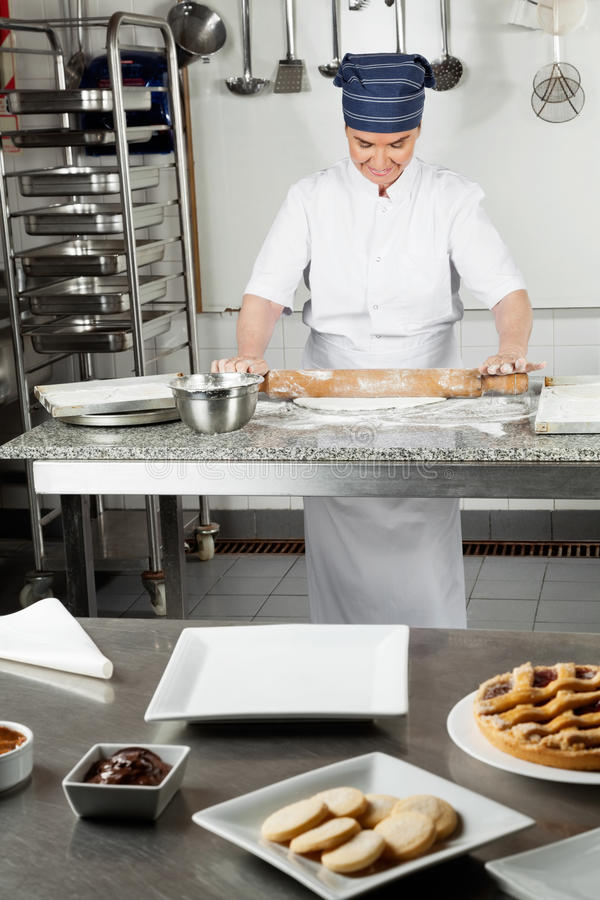 Chef Rolling Dough With Sweet Food In Foreground royalty free stock images