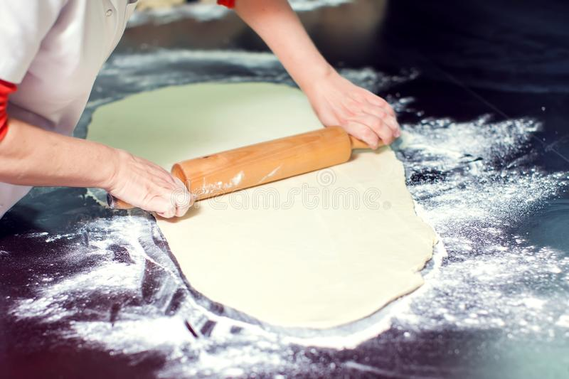 A woman rolls out the doughon on black table royalty free stock photos