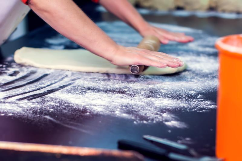 A woman rolls out the doughon on black table stock image