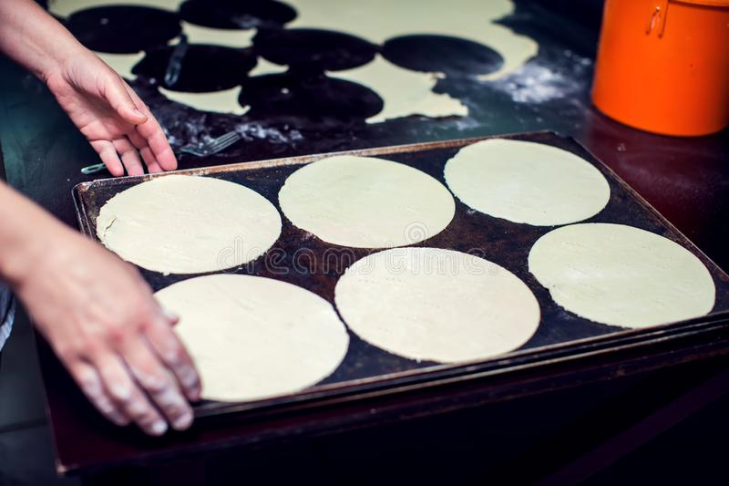 A woman rolls out the doughon on black table royalty free stock photography