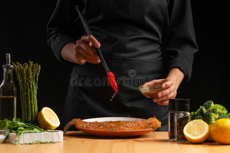 Chef rubs seafood, red fish salmon or trout marinade juice, Asian cuisine, a recipe book, on a black background. Preparing tasty. And healthy food royalty free stock photo