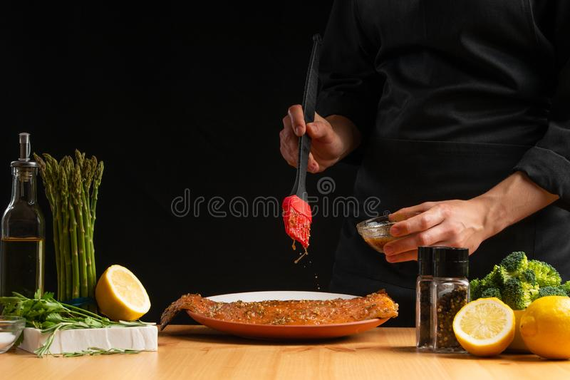 Chef rubs seafood, red fish salmon or trout marinade juice, Asian cuisine, a recipe book, on a black background. Preparing tasty. And healthy food royalty free stock image