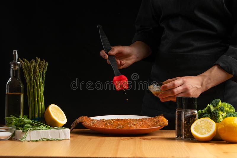 Chef rubs seafood, red fish salmon or trout marinade juice, Asian cuisine, a recipe book, on a black background. Preparing tasty. And healthy food stock photography
