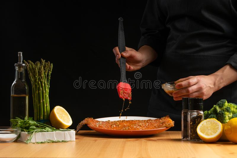 Chef rubs seafood, red fish salmon or trout marinade juice, Asian cuisine, a recipe book, on a black background. Preparing tasty. And healthy food stock photos