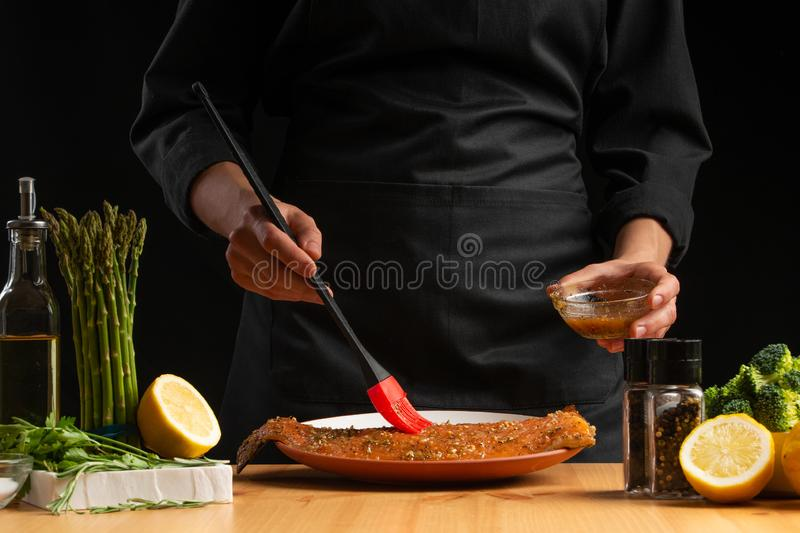 Chef rubs seafood, red fish salmon or trout marinade juice, Asian cuisine, a recipe book, on a black background. Preparing tasty. And healthy food royalty free stock photos
