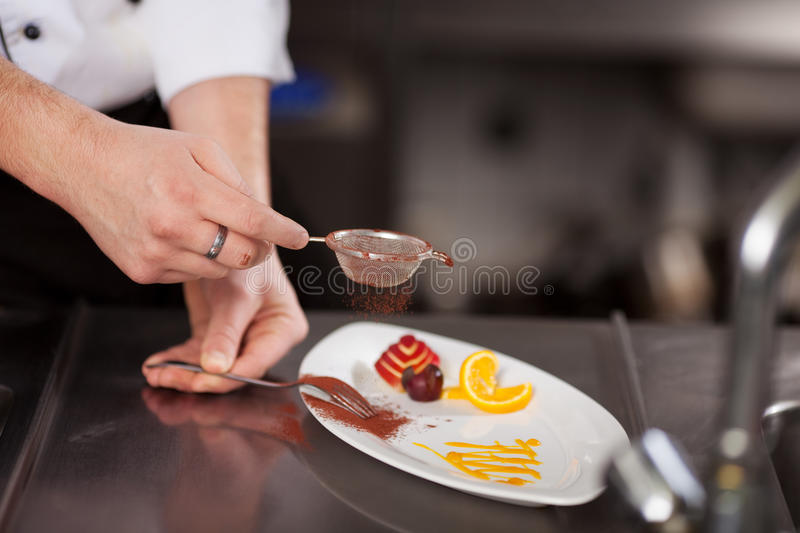 Chef's Hand Sieving Coco Powder In Plate At Kitchen Counter. Closeup of chef's hand sieving coco powder in plate at commercial kitchen counter stock photos