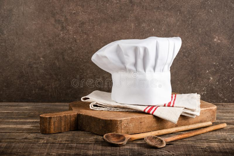Chef`s hat, antique cutting board and wooden spoons stock photo