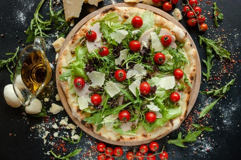 Chef`s pizza special restaurant meal. Chef`s pizza with meat and vegetables. Special restaurant meal concept royalty free stock photography
