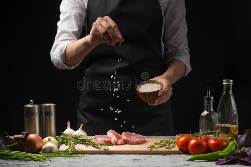 Chef salts steak grill pan. Preparing fresh beef or pork. Horizontal photo with a dark black background. Chef salts steak grill pan. Preparing fresh beef or stock photography