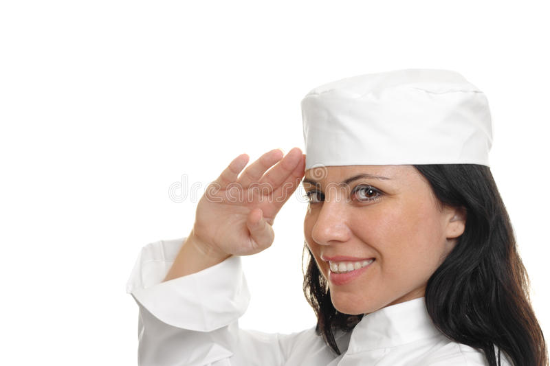 Chef Saluting on white. A female chef saluting and smiling. She is on a white background stock image