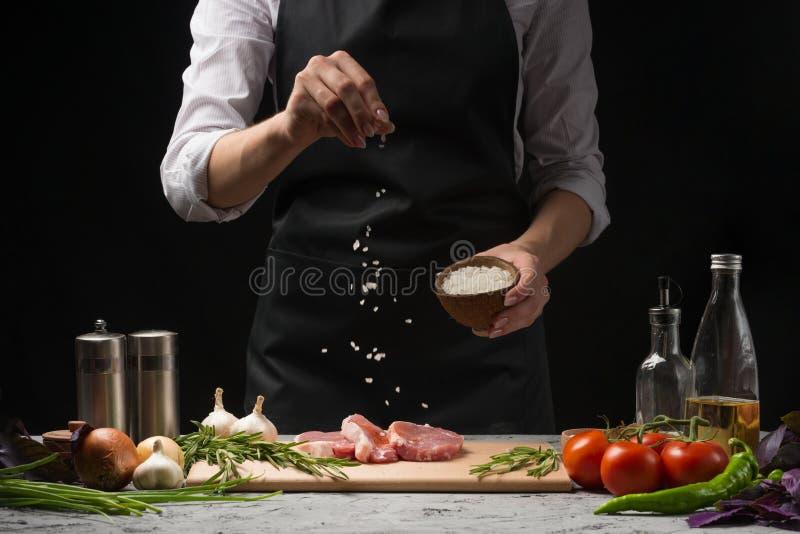 Chef salzt Steakgrillwanne Zubereitung des frischen Rindfleisches oder des Schweinefleisch Horizontales Foto mit einem dunklen sc stockfotografie