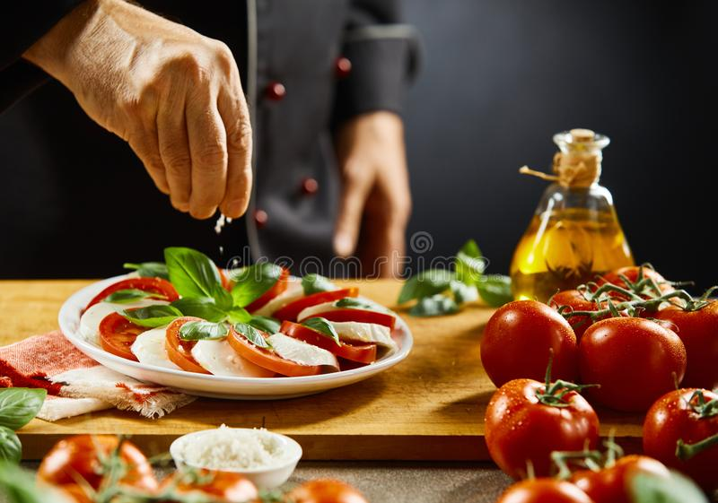 Chef seasoning a Caprese salad with salt stock images