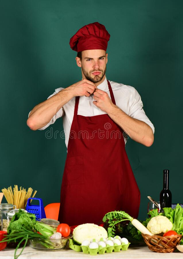 Chef with serious face adjusts collar on dark green background. stock photography