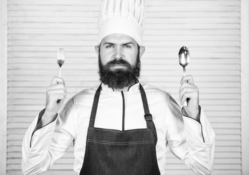 Chef serious face hold spoon and fork. Man handsome with beard holds kitchenware on white background. Cooking process royalty free stock images