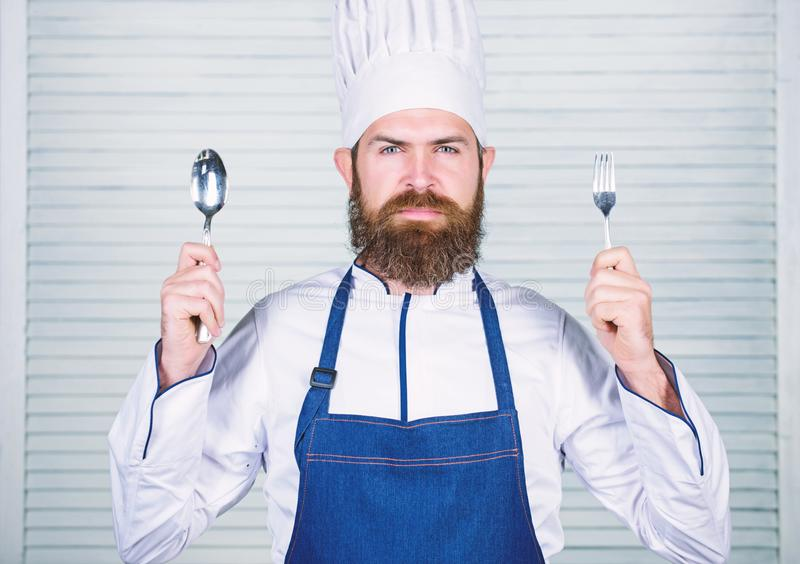Chef serious face hold spoon and fork. Man handsome with beard holds kitchenware on white background. Cooking process royalty free stock photography