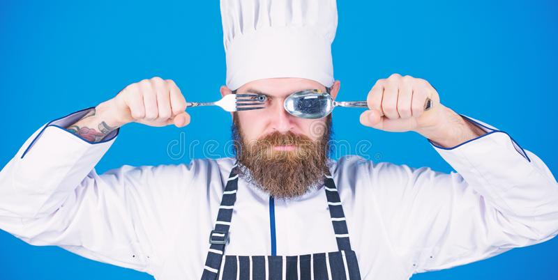 Chef serious strict face hold spoon and fork. Man handsome with beard holds kitchenware on blue background. Cooking stock photography