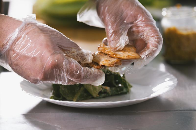 Chef serves fried chicken on the plate in restaurant royalty free stock image