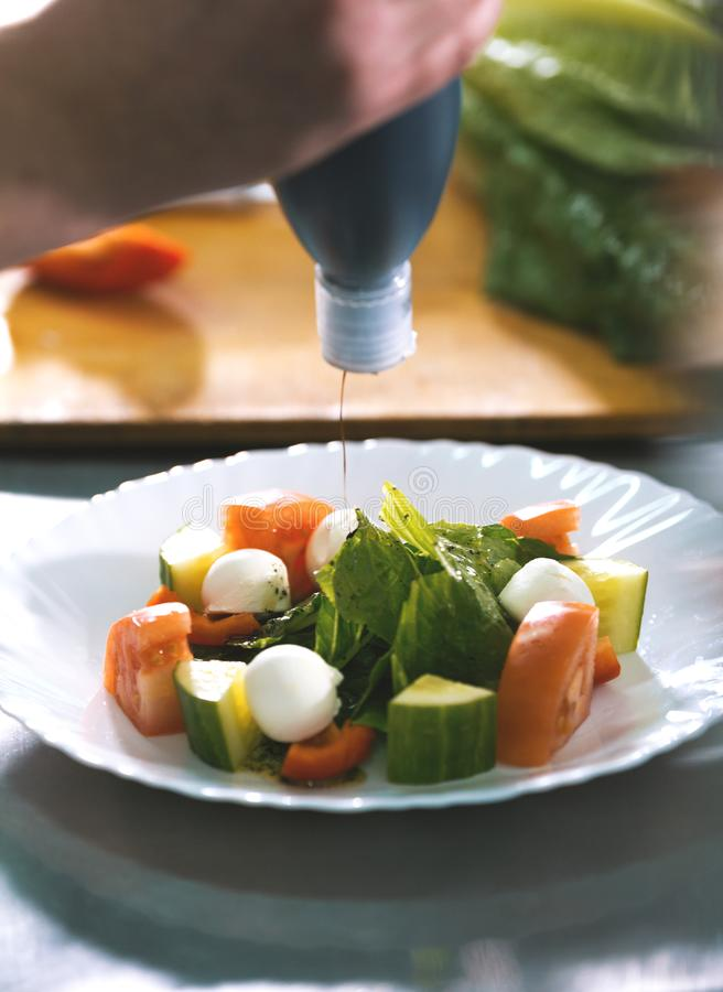 Chef serves greek salad on the plate in restaurant royalty free stock image