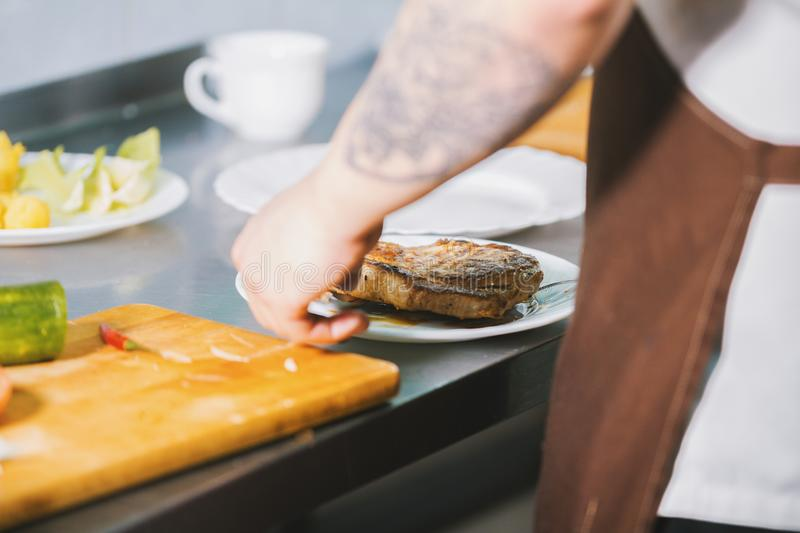 Chef serves meat on the plate in restaurant royalty free stock image