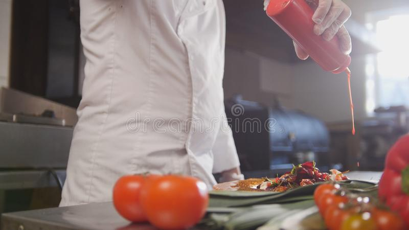 Chef serves the salad adding the sauce, fresh vegetables in the foreground stock image