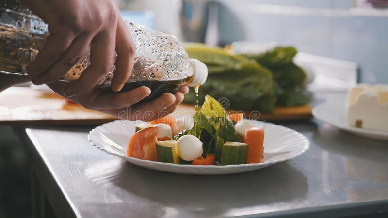 Chef serves salad on the plate in restaurant royalty free stock photo