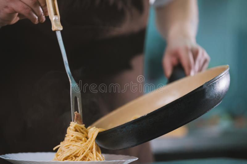 Chef serves spaghetti on the plate in restaurante stock photography