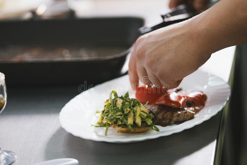 Chef serves steak in restaurant stock image