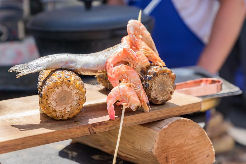 Chef serves wooden desk with seafood and sweet grilled corn at the festival. Street food prepared on grill stock photos