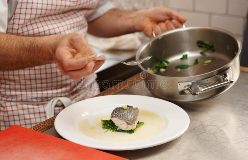 Chef is serving steamed seabass stock image