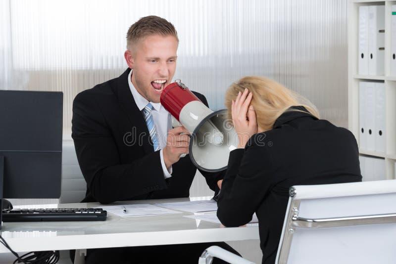 Chef- Shouting At Businesswoman door Luidspreker in Bureau royalty-vrije stock fotografie
