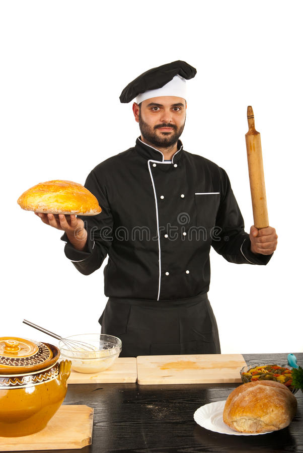 Chef showing bread and rolling pin. Chef man showing bread and rolling pin in kitchen royalty free stock image