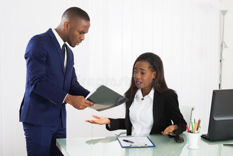 Chef Showing Document To ihre weibliche Exekutive stockbild