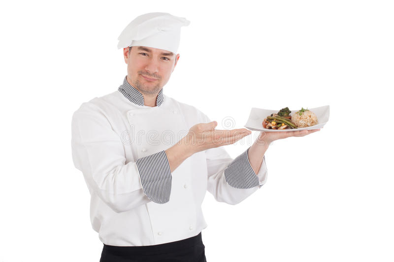 Chef showing and holding a plate of prepared food. Smiling chef showing and holding a plate of prepared food. Isolated on white background stock images