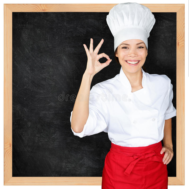 Chef showing menu blackboard and Perfect hand sign. Woman in front of blank menu blackboard. Happy female chef, cook or baker by empty chalkboard menu display royalty free stock images