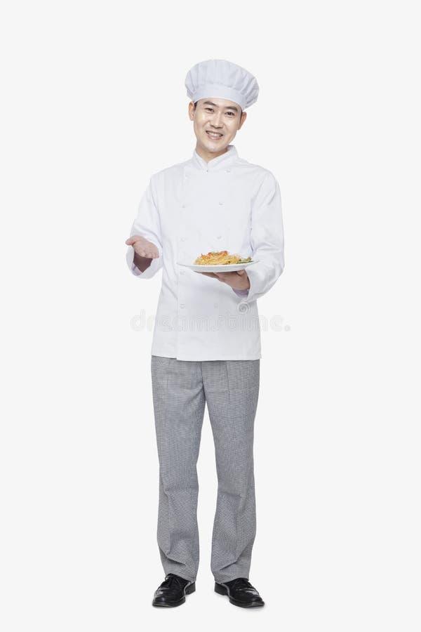 Chef showing prepared food, studio shot stock photography