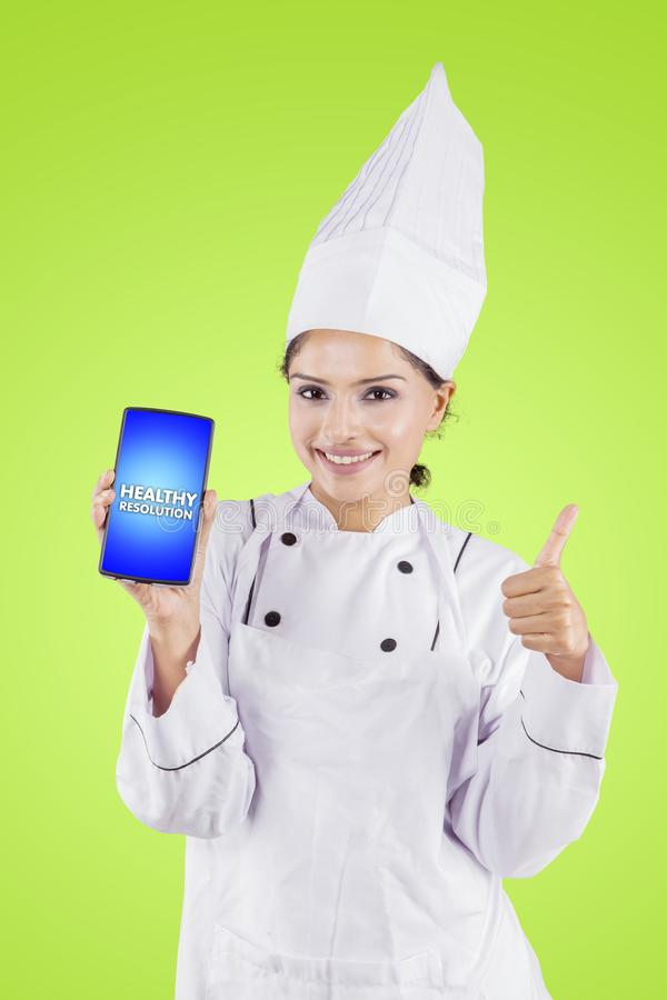 Chef shows thumb up and healthy resolution text. Happy female chef showing thumb up and healthy resolution text on a smartphone in the studio stock photography