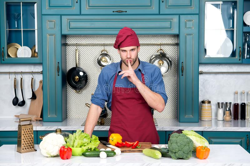 Chef with silence gesture finger at table with vegetables. Man cook secret dish in kitchen. Ingredients for cooking vegan food. Ve stock photography
