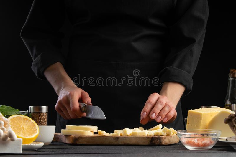Chef slices mazzarella cheese to prepare a delicious and fresh salad. Vegetarian and fresh food, gastronomy and cooking, recipe. Book and recipes. On a black stock photography