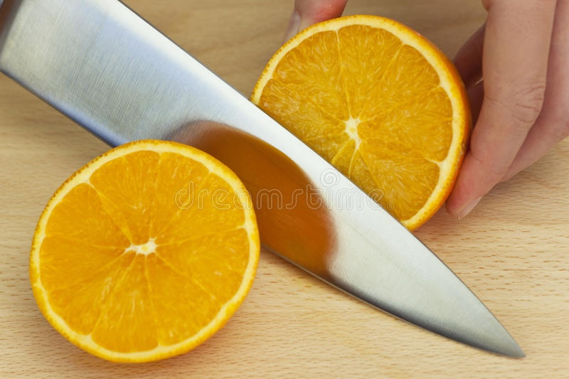Chef Slicing Fresh Orange With Sharp Kitchen Knife. Close up on the hands of a chef slicing a fresh orange in half with a sharp kitchen knife royalty free stock image
