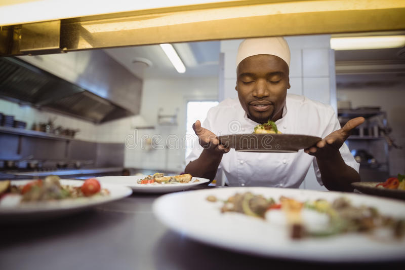 Chef smelling food in commercial kitchen. At restaurant royalty free stock photo