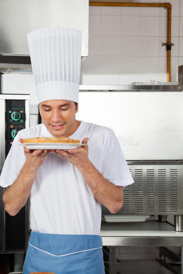 Chef Smelling Sweet Dish In Kitchen stock images