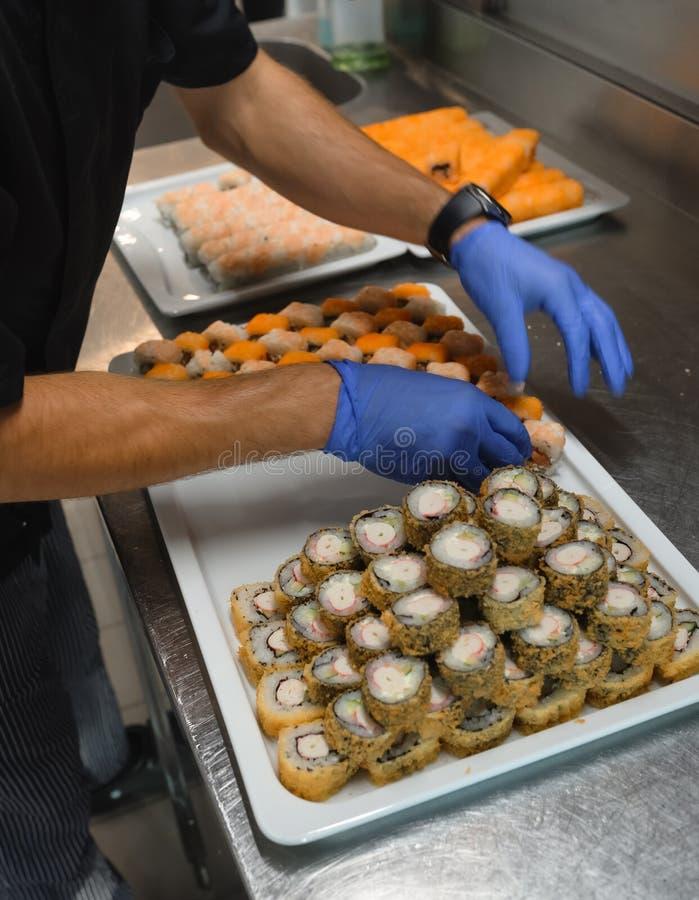 Chef som arrangerar sushi-rullar i restaurangköket, cateringverksamhet royaltyfria bilder