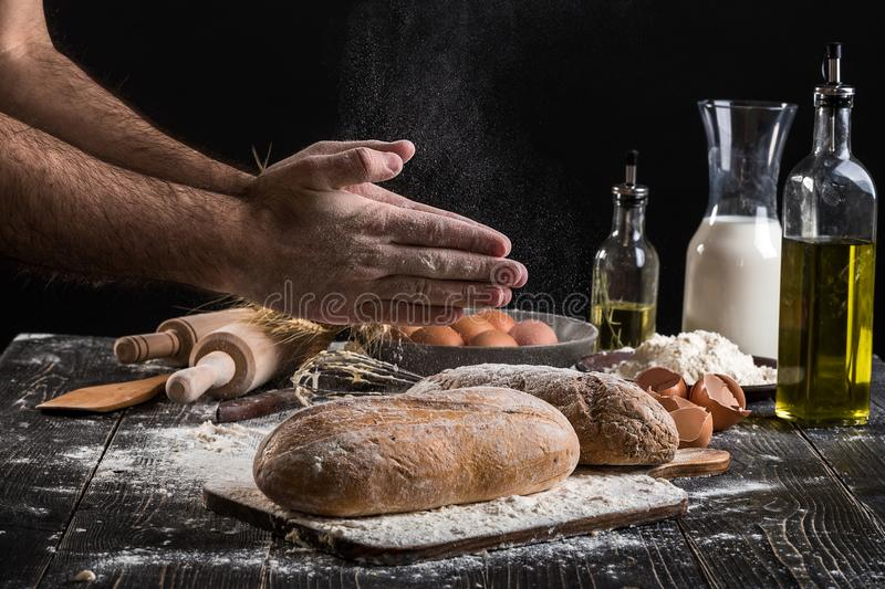 Chef sprinkles fresh bread with flour. Man preparing dough at table in kitchen. On black background. Healthy or cooking concept stock photo