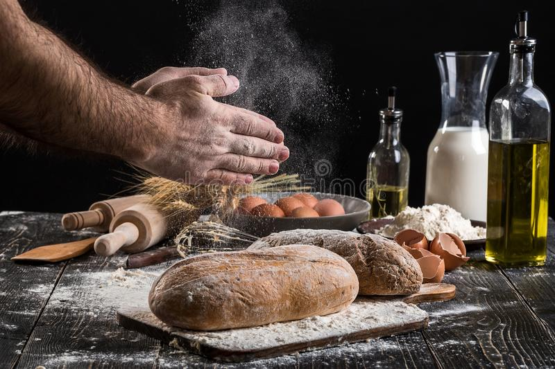 Chef sprinkles fresh bread with flour. Man preparing dough at table in kitchen. On black background. Healthy or cooking concept royalty free stock image