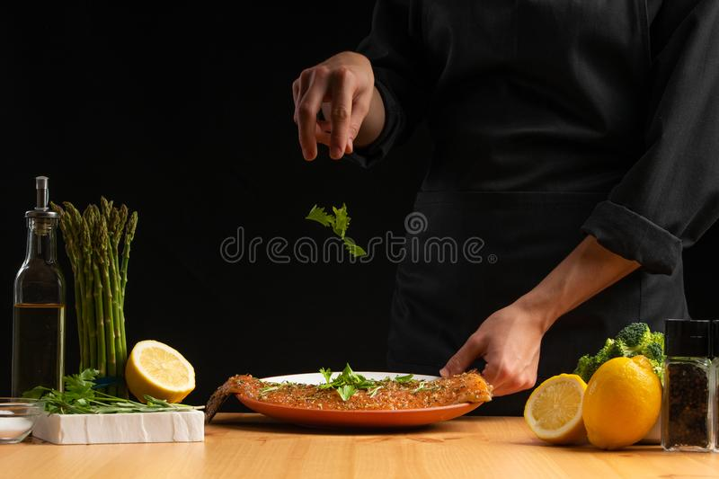Chef sprinkles parsley seafood, red salmon or trout fish, freeze in motion, Asian cuisine, recipe book, on black background. Preparing tasty and healthy food royalty free stock photo