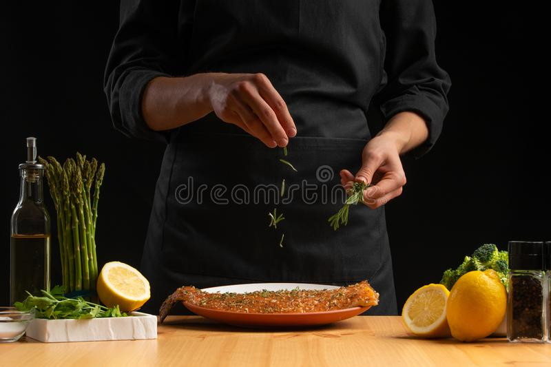 Chef sprinkles rosemary seafood, red salmon or trout fish, freeze in motion, Asian cuisine, recipe book, on black background. Preparing tasty and healthy food royalty free stock image