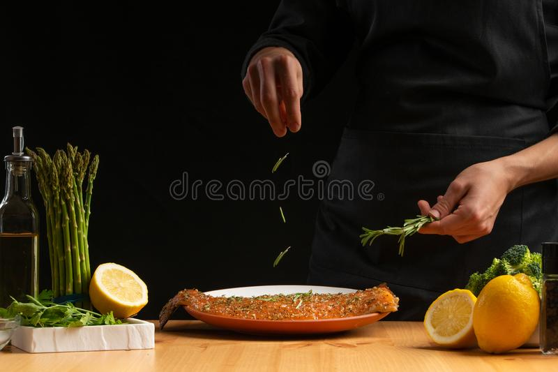 Chef sprinkles rosemary seafood, red salmon or trout fish, freeze in motion, Asian cuisine, recipe book, on black background. Preparing tasty and healthy food stock images