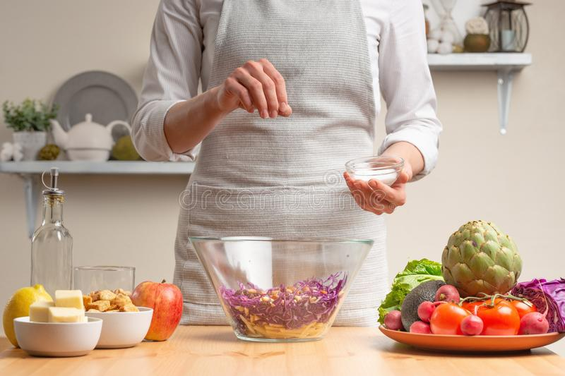 Chef sprinkles salt on salad, stir, in the process of a vegetarian salad with the hand of the chef in the home kitchen.Healthy royalty free stock photography