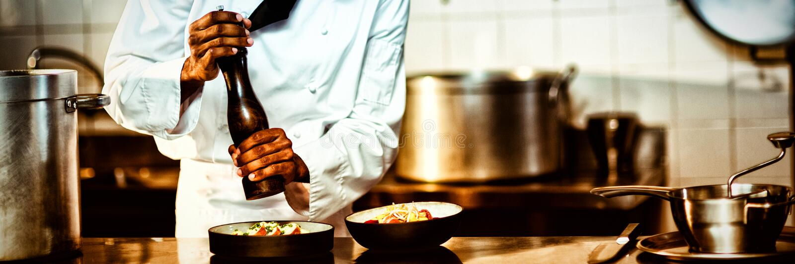 Chef sprinkling pepper on a meal. In commercial kitchen stock image